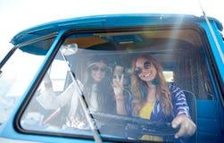 Smiling young hippie women driving minivan car Stock Photo