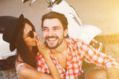 Smiling young hipster couple whispering gossip stock photo