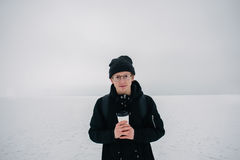 Smiling young hipster guy dressed in black sunglasses and winter on snow-covered lake and a cup of coffee in hand. Smiling young hipster guy dressed in black on Stock Photo