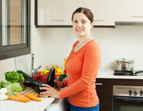 Smiling young housewife  with aubergines Royalty Free Stock Photography