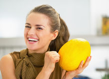 Smiling young housewife checking ripeness of melon Royalty Free Stock Photo