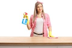 Smiling young housewife cleaning a wooden counter and holding a cleaning supply royalty free stock image