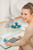 Smiling young housewife with credit card using tablet pc Royalty Free Stock Images