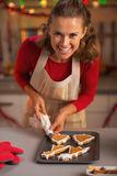 Smiling young housewife decorating christmas cookies in kitchen Stock Photo