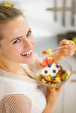 Smiling young housewife eating fresh fruit salad. rear view. Smiling young housewife eating fresh fruit salad  in modern kitchen. rear view Stock Photos