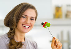 Smiling young housewife eating vegetables Stock Image