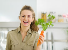 Smiling young housewife holding carrot in kitchen Stock Photography