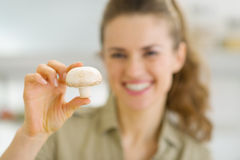Smiling young housewife holding mushroom Royalty Free Stock Image