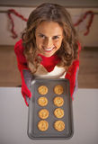 Smiling young housewife holding pan with christmas cookies Stock Images