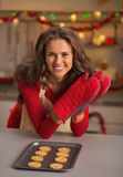 Smiling young housewife in kitchen gloves and pan with cookies Royalty Free Stock Photo