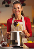 Smiling young housewife making apple in chocolate glaze Royalty Free Stock Photos