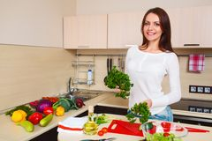 Smiling young housewife mixing fresh salad Royalty Free Stock Photos