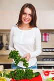 Smiling young housewife mixing fresh salad Royalty Free Stock Photography