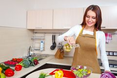 Smiling young housewife mixing fresh salad Stock Photo