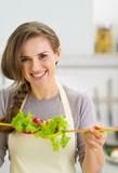 Smiling young housewife mixing fresh salad with spoons Stock Photography