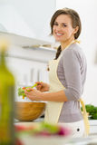 Smiling young housewife mixing salad in kitchen Stock Photo