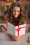 Smiling young housewife reading christmas postcard in kitchen Royalty Free Stock Images