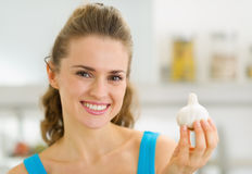 Smiling young housewife showing garlic Stock Photos