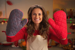 Smiling young housewife showing kitchen gloves Stock Photo