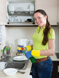 Smiling young housewife washing dishes Stock Photo