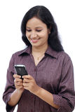 Smiling young Indian business woman text messaging Royalty Free Stock Photography