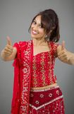 Smiling young Indian woman showing thumb up sign with both hands Stock Images
