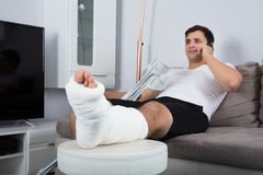 Smiling Young Injured Man Talking On Mobile Phone royalty free stock photo