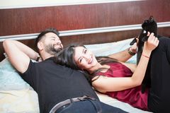 Young inlove couple on the bed with their cats Royalty Free Stock Photography