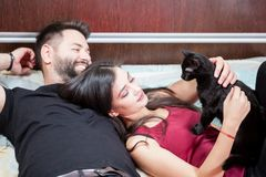 Young inlove couple on the bed with their cats Stock Photography