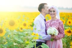 Smiling young islamic couple portrait on sunflowers field. Muslim marriage.  Royalty Free Stock Photos