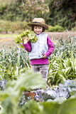 Smiling young kid loving to harvest organic vegetable from garden Royalty Free Stock Images