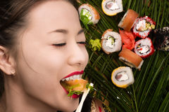 Smiling young Korean girl eating sushi rolls Stock Image