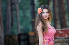 Smiling young lady with attached flower in hair. Beautiful young lady with attached flower in hair looking away with a true big smile. Blurry pines as background Stock Image
