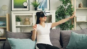 Smiling young lady in augmented reality glasses is moving hands and turning head sitting on sofa at home and having fun. Entertainment and modern technology stock footage