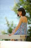 Smiling young lady on a bench in a park Stock Image