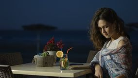 Smiling young lady drinking cocktail at seaside restaurant, writing in notebook. Stock footage stock video footage