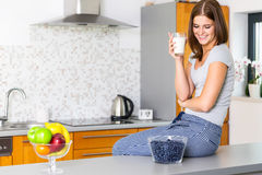 Smiling young lady with  glass of milk. Siting in kitchen Stock Photos
