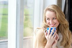 Smiling young lady holding cup of tea royalty free stock photo