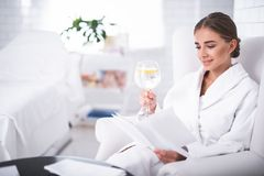 Free Smiling Young Lady Holding Glass Of Lemon Water While Reading Booklet Royalty Free Stock Image - 124771836