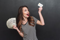 Smiling young lady holding money and debit card in hands. Picture of smiling young lady standing over grey wall and holding money and debit card in hands stock image