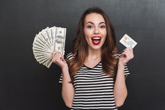 Smiling young lady holding money and debit card in hands Stock Photography