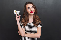 Smiling young lady over grey wall holding debit card. Image of smiling young lady standing over grey wall and holding debit card in hands. Looking at camera stock photography