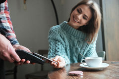 Smiling young lady pays for her order with phone. Stock Image