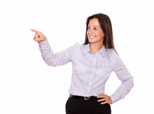 Smiling young lady pointing while standing Royalty Free Stock Image