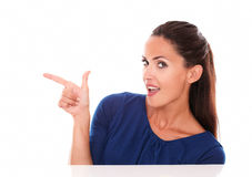 Smiling young lady pointing to her right Royalty Free Stock Photo