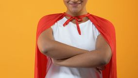 Smiling young lady in red cape on bright background, powerful wonder woman stock video