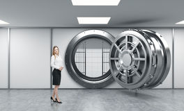 Smiling young lady standing in front of a big unlocked round met Stock Photos