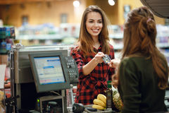 Smiling young lady standing in supermarket holding credit card Royalty Free Stock Image