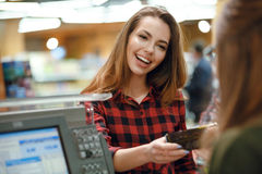 Smiling young lady standing in supermarket shop Stock Image