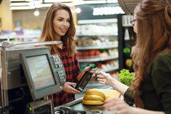 Smiling young lady standing in supermarket shop Stock Images